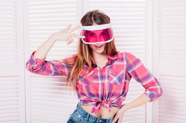 Peinzend tienermeisje geruit overhemd dragen en honkbal glb die omhoog in gedachten over roze achtergrond kijken
