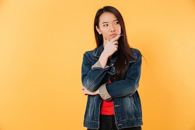 Peinzende aziatische vrouw in de kin van de jasjeholding en weg het kijken