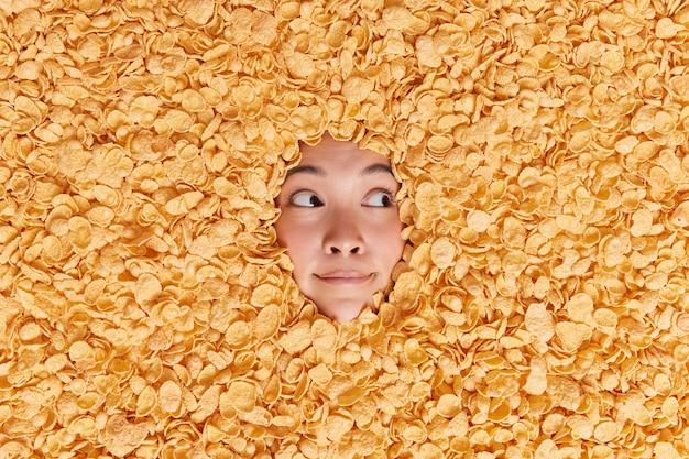 Peinzende aziatische vrouw kijkt weg met doordachte uitdrukking verdronken in droge cornflakes die gezond gaan ontbijten, denkt aan iets en kijkt aandachtig naar rechts