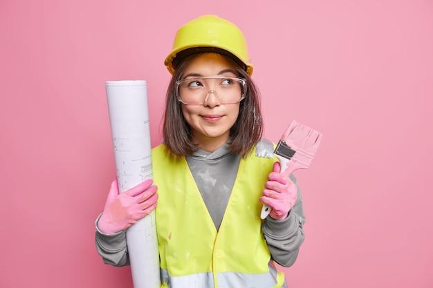 Peinzende aziatische vrouwelijke onderhoudsmedewerker houdt opgerolde blauwdruk-schilderborstel vast en kijkt bedachtzaam weg en draagt uniforme poses op roze