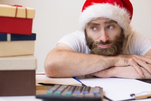 Peinzende bedrijfsmens die kerstmanhoed en het ontspannen draagt