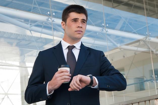 Peinzende bedrijfsmens die tijd op horloge in openlucht controleert