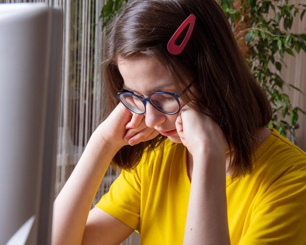 Peinzende blanke student in een geel t-shirt denkt, lijdt, drukt haar handen voor haar gezicht. afstand leren. studeer 's avonds.
