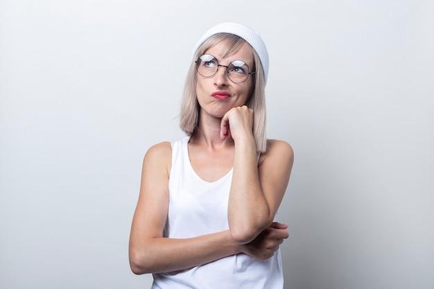 Peinzende blonde jonge vrouw in glazen op een lichte achtergrond.