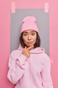 Peinzende duizendjarige aziatische vrouw houdt kin vast met twijfelachtige uitdrukking, overweegt interessante suggestie gekleed in casual hoodie en hoed poseert tegen roze muur met gepleisterd vel papier
