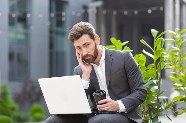 Peinzende en gefocuste mannelijke zakenman die op afstand op de computer werkt voordat hij een moeilijke beslissing neemt terwijl hij in de buurt van kantoor zit voor een sollicitatiegesprek