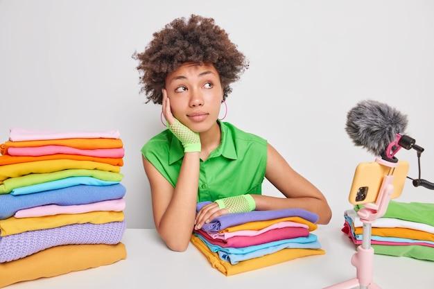 Peinzende etnische huishoudster kijkt weg en denkt nadenkend over nieuwe inhoud voor haar videoblog omringd door netjes opgevouwen wasgoed zit aan tafel tegen wit