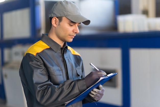 Peinzende fabrieksarbeider die op een document schrijft