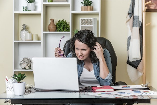 Peinzende freelancer die laptop thuis met behulp van