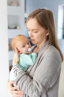 Peinzende geconcentreerde nieuwe moeder die baby houdt