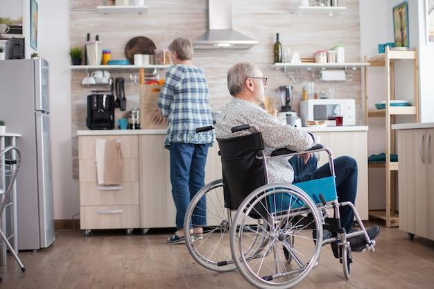 Peinzende gehandicapte bejaarde in rolstoel die vanuit de keuken op het raam kijkt gehandicapte man zit in een rolstoel in de keuken en kijkt door het raam terwijl zijn vrouw het ontbijt klaarmaakt. ongeldig, p