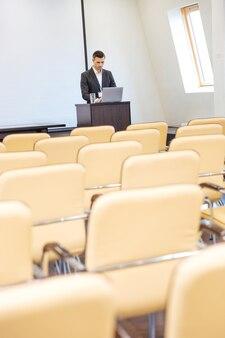 Peinzende gerichte zakenman die op de tribune staat en een laptop gebruikt in een lege vergaderzaal