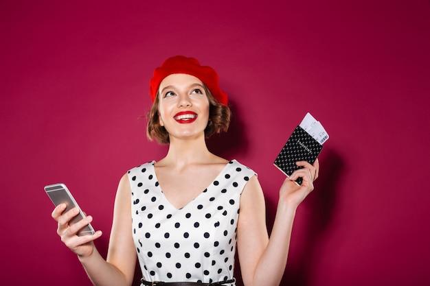 Peinzende glimlachende gembervrouw in smartphone van de kledingsholding en paspoort met kaartjes terwijl het kijken omhoog over roze