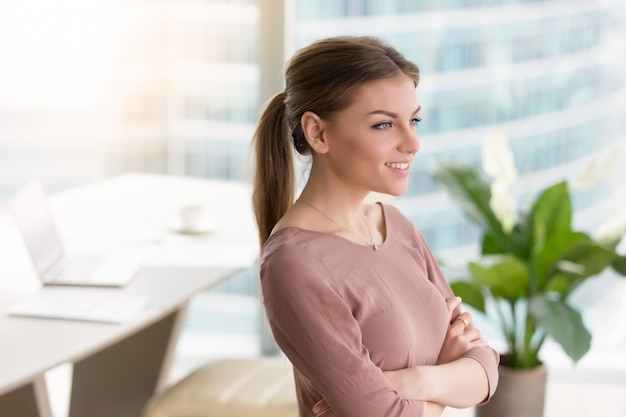 Peinzende glimlachende jonge vrouw die venster, gekruiste wapens bekijkt, binnen