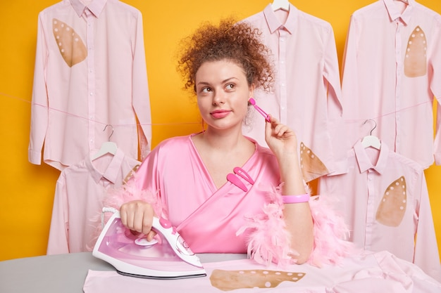 Peinzende goed uitziende gekrulde huisvrouw houdt hand op oorbel kijkt weg met doordachte uitdrukking maakt gebruik van elektrisch ijzer om kleding te strijken gekleed in huiselijk gewaad poseert tegen gele muur