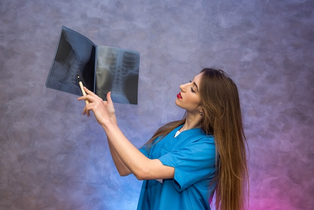 Peinzende jonge arts die röntgenfoto's onderzoekt en een diagnose stelt. medisch concept