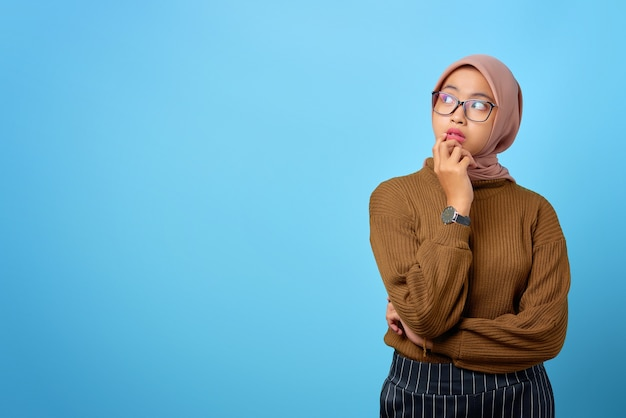 Peinzende jonge aziatische vrouw kijkt serieus na over een vraag op een blauwe achtergrond