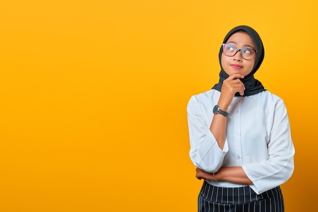 Peinzende jonge aziatische vrouw kijkt serieus na over een vraag op gele achtergrond