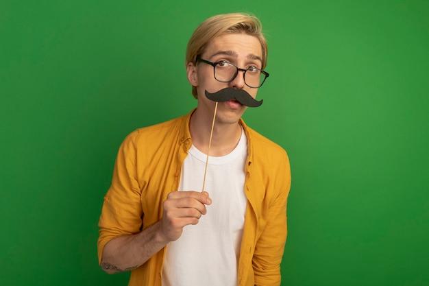 Peinzende jonge blonde kerel die gele t-shirt en bril draagt die valse snor op stok houdt die op groen wordt geïsoleerd