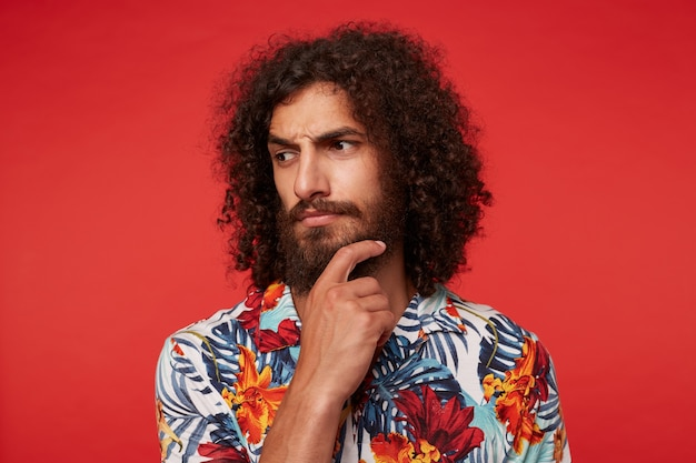 Peinzende jonge brunette gekrulde man met weelderige baard peinzend opzij kijkend en fronsende wenkbrauwen, met opgeheven hand op zijn kin