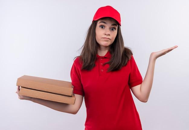 Peinzende jonge leveringsvrouw die rode t-shirt in rood glb draagt die een pizzadoos op geïsoleerde witte muur houdt