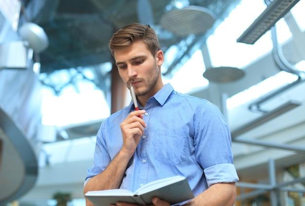 Peinzende jonge man die in zijn kantoor staat