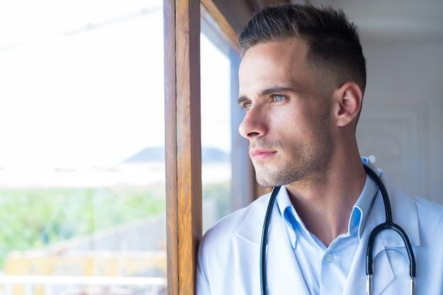 Peinzende jonge mannelijke blanke arts in wit medisch uniform kijk in vensterafstand denken of nadenken, serieuze man gp plan toekomstige carrière of succes in de geneeskunde, visualiseren op het werk schrijven