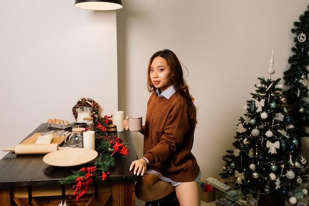 Peinzende jonge mooie aziatische vrouw met brandende kaarsen op kerstavond die wens maakt