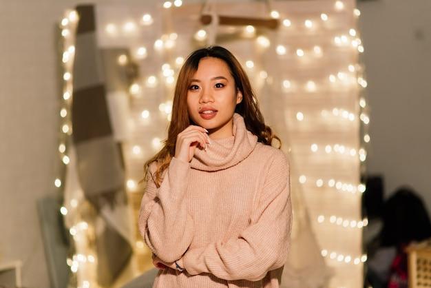 Peinzende jonge mooie aziatische vrouw met brandende kaarsen op kerstavond die wensen maakt