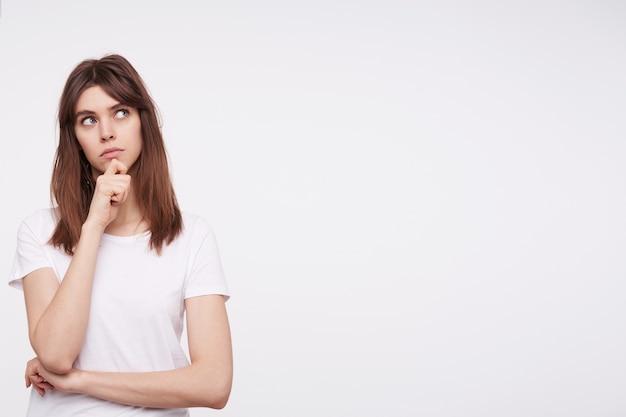 Peinzende jonge mooie brunette vrouw houdt haar kin vast met opgeheven hand terwijl ze bedachtzaam naar boven kijkt, haar lippen gevouwen terwijl ze over een witte muur staat
