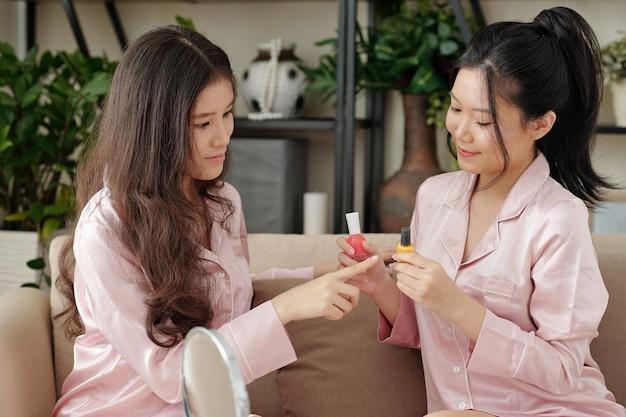 Peinzende jonge mooie vrouw die de kleur van nagellak kiest in handen van haar vriend