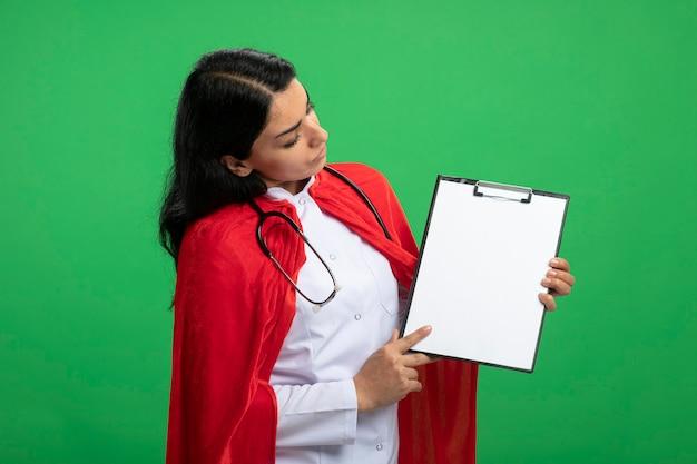 Peinzende jonge superheld meisje medische gewaad met stethoscoop houden en kijken naar klembord geïsoleerd op groen