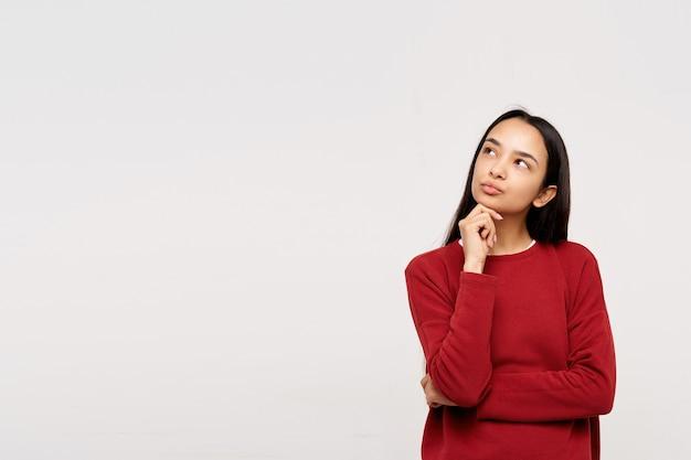 Peinzende jonge vrij langharige brunette vrouw die haar kin vasthoudt met opgeheven hand en lippen tuit terwijl ze naar boven kijkt, staande over een witte muur