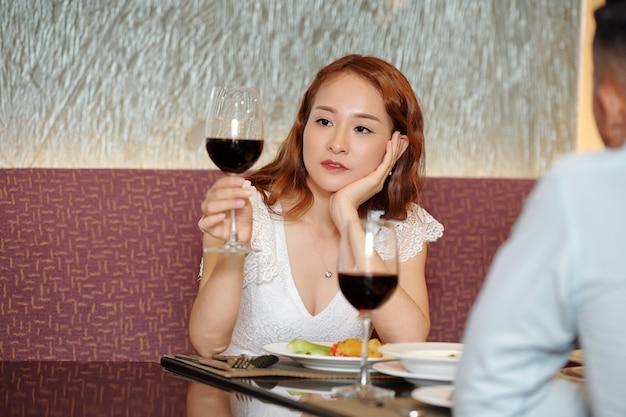 Peinzende jonge vrouw die naar een glas wijn kijkt terwijl ze luistert naar saaie verhalen over haar vriendin