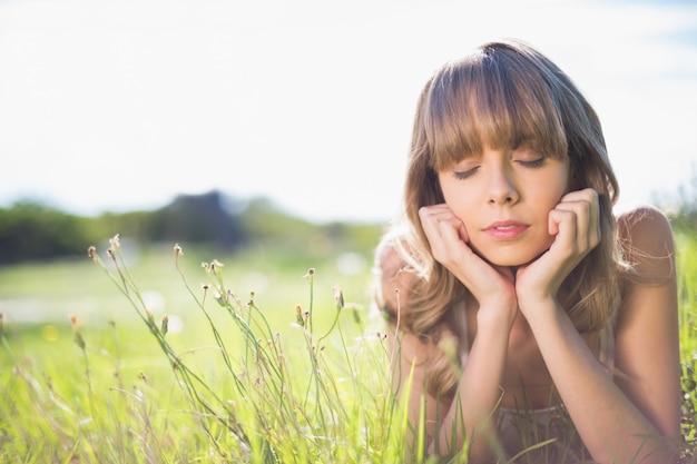 Peinzende jonge vrouw die op het gras ligt