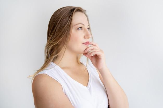 Peinzende jonge vrouw die weg kijkt