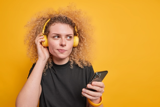 Peinzende jonge vrouw met krullend haar draagt stereohoofdtelefoon op oren luistert favoriete muziek maakt gebruik van mobiele telefoontoepassing draagt casual zwarte t-shirt poses tegen gele muur met lege ruimte