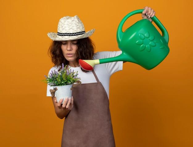 Peinzende jonge vrouw tuinman in uniform dragen tuinieren hoed drenken bloem in bloempot met gieter geïsoleerd op oranje