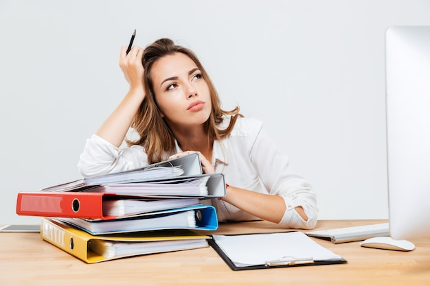 Peinzende jonge zakenman zit aan het bureau en houdt pen geïsoleerd op de witte achtergrond
