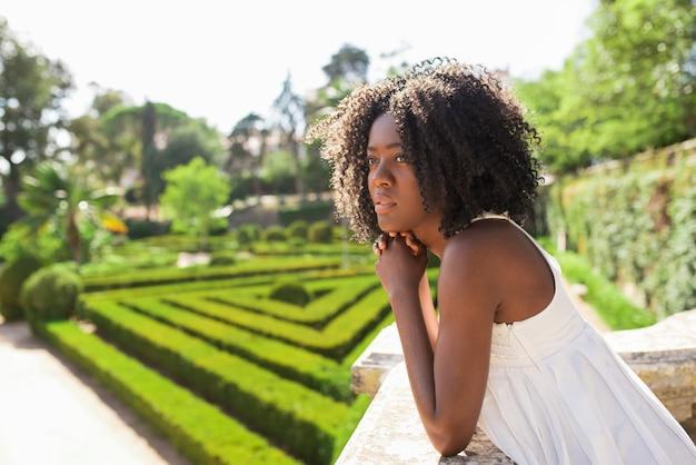 Peinzende jonge zwarte vrouw ontspannen in park