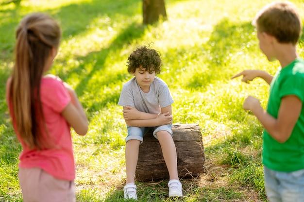 Peinzende jongen zittend op boomstronk en vrienden
