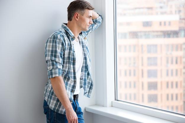 Peinzende knappe man in geruit hemd en spijkerbroek die bij het raam staat en denkt
