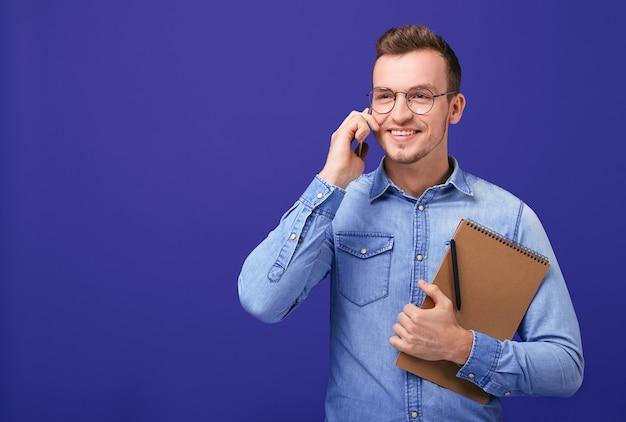 Peinzende knappe zakenman sprekende telefoon met in hand notitieboekje