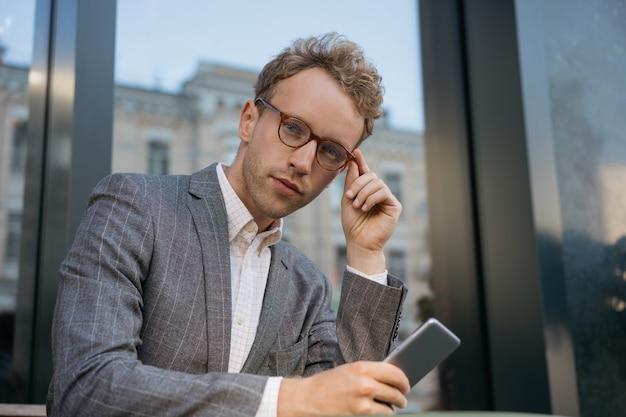 Peinzende man die een mobiele telefoon gebruikt die naar de camera kijkt portret van een knappe manager die een bril draagt