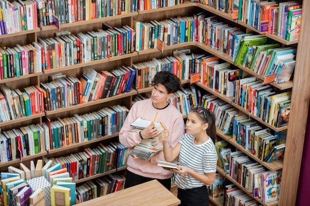 Peinzende man en zijn slimme klasgenoot kijken naar grote boekenplank in de universiteitsbibliotheek terwijl het meisje naar een van de boeken wijst