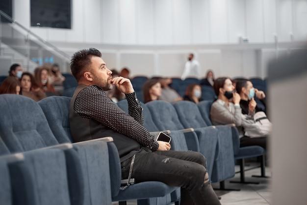 Peinzende man met een smartphone die in de collegezaal zit
