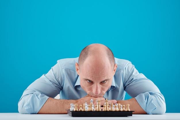 Peinzende man van middelbare leeftijd die op tafel leert en naar het schaakbord voor hem kijkt
