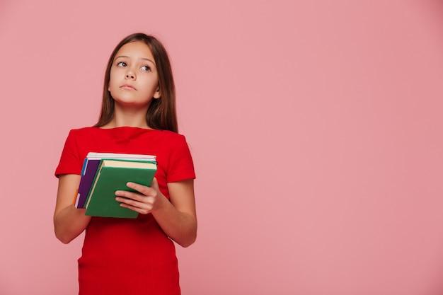 Peinzende meisjesleerling die exemplaarruimte bekijkt en boeken houdt