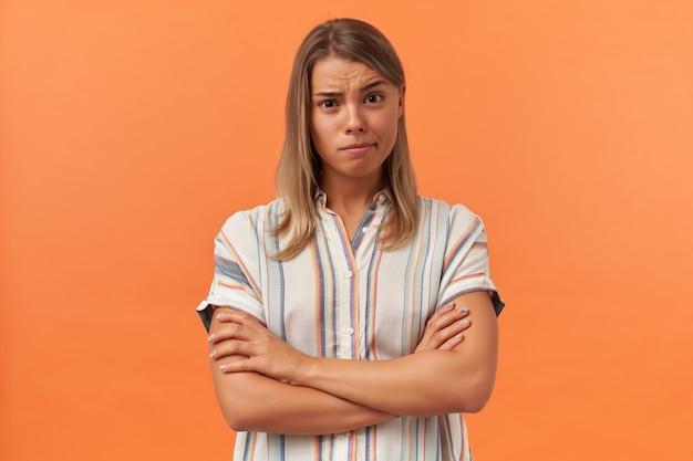 Peinzende mooie jonge vrouw in gestreept shirt staande en houden armen gekruist geïsoleerd over oranje muur
