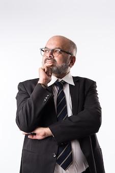 Peinzende nadenkende indische oude zakenman. kin aanraken. aziatische senior kale en bebaarde zakenman denken tegen een witte achtergrond thinking